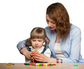 Young mother and her daughter modelling with plasticine — Stock Photo