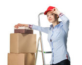 Smiling young woman resting near a pile of boxes — Stock Photo