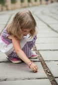 Little girl drawing on concrete pavement — Stock Photo