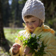 Little girl with bouquet outdoors — Stock Photo