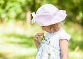 Little girl playing with thorny plant — Stock Photo