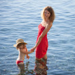 Stock Photo: Happy mother and daughter walking near seashore