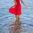Stock Photo: Womin red dress walking near seashore