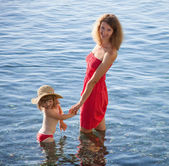 Happy mother and daughter walking near the seashore — Stock Photo
