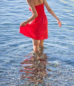 Woman in red dress walking near the seashore — Stock Photo