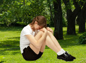 Woman doing exercises sitting on grass — Stock Photo