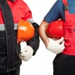 Two builders in uniform holding hardhats isolated on white — Stock Photo