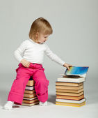 A little girl sitting among books — Stock Photo