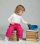 Baby sitting on stacked books — Stock Photo