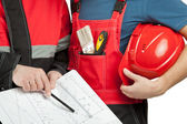 Workers in uniform discussing design of construction project — Stock Photo