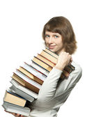 The smiling girl holding a big stack of books — Stock Photo