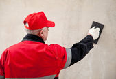 Plasterer in uniform working with float against the wall — Stock Photo