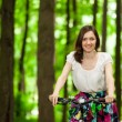 Happy young girl on bicycle in summer park — Stock Photo