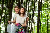Happy beautiful young couple on bicycle — Stockfoto