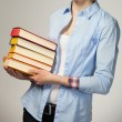 Unrecognizable girl holding a stack of books, grey background — Stock Photo