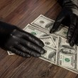 Human hands in black gloves holding dollars — Stock Photo