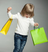 Smiling little girl looking on multicolored shopping bags — Stock Photo