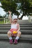 Glad flicka sitter på stegen — Stockfoto