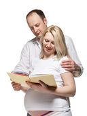Glad gravid kvinna med sin man läser en bok — ストック写真