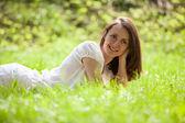 Mooi meisje liggend op een groen gras — Stockfoto