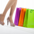 Beautiful woman's legs and multicolored shopping bags — Stock Photo