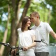 Romantic young couple walking with bicycles — Stock Photo