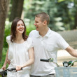 Happy young couple walking in a park with bicycles — Stock Photo