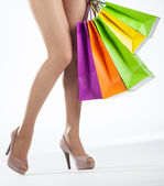 Female legs and multicolored shopping bags — Stock Photo