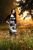 Beautiful young brunette posing in a park — Stock Photo