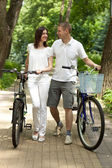 Happy young couple walking with bicycles — Stock Photo