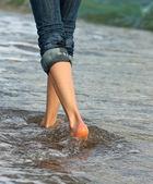 Woman's legs walking along the seacoast — Foto de Stock