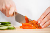 Female hands cutting fresh cucumber and tomato — Stock Photo