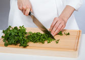 Cook chopping fresh parsley — Stock Photo