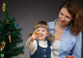 Happy smiling baby girl and her mummy decorates the Christmas tree — Stock Photo