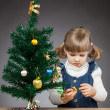 Little girl decorates the Christmas tree — Stok fotoğraf