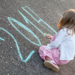 Little girl writing 2014 on asphalt — Stock Photo