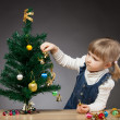 Little girl decorates the Christmas tree — 图库照片