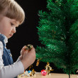 Little girl decorates the Christmas tree — Stockfoto #35652953