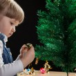 Little girl decorates the Christmas tree — Stock fotografie #35652953