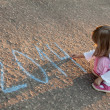 Stock Photo: Little girl writing 2014 on asphalt