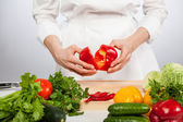 Cook's hands preparing salad — Stock Photo