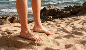 Legs on sunny beach — Stock Photo