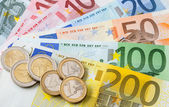 Many euro banknotes and coins — Stock Photo