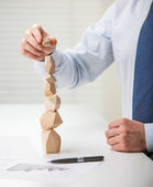 Businessman putting last block to the tower — Stock Photo