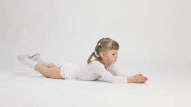 Pretty little girl lying on the floor and doing exercise — Stock Video