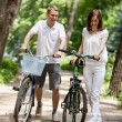 Happy young couple walking with bicycles in a park — Stock Photo