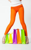 Woman's legs in orange pants and shopping bags — Stock Photo