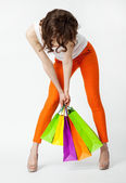 Unrecognizable brunette in orange pants holding shopping bags — Stock Photo