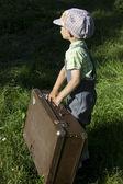 En pojke bär en resväska — Stockfoto