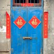 Old blue Chinese door with red good fortune posters — Stock Photo